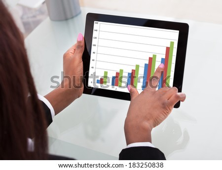 Cropped image of businesswoman analyzing comparison graph on digital tablet at desk in office - stock photo