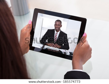Cropped image of businesswoman attending video conference with colleague on digital tablet at desk in office