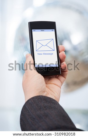 Cropped image of businesswoman's hand holding smartphone with new message on screen - stock photo