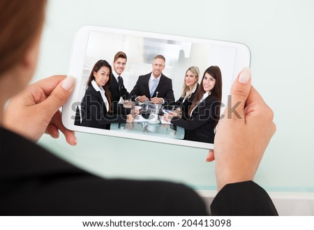 Cropped image of businesswoman video conferencing with team on digital tablet at desk in office