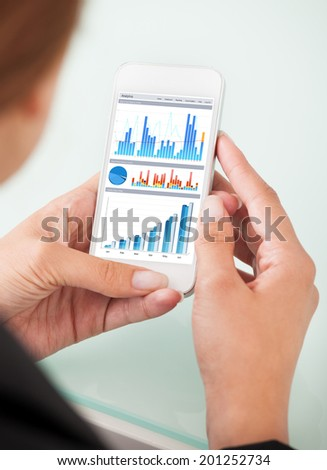 Cropped image of businesswoman watching financial charts on smartphone in office - stock photo
