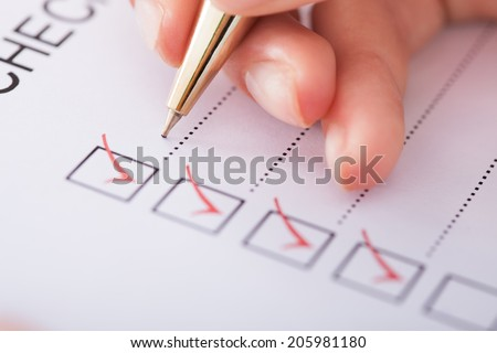 Cropped image of businesswoman writing on checklist - stock photo