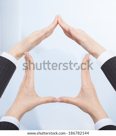 Cropped image of businesswomen's hands forming house structure in office