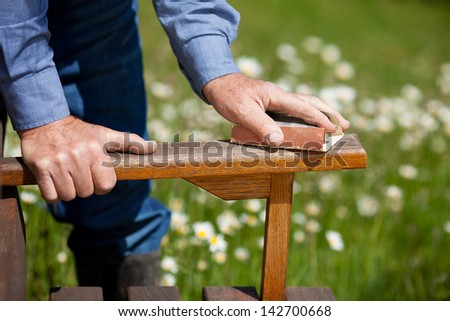 Cropped image of carpenter's hands polishing wood in park - stock photo