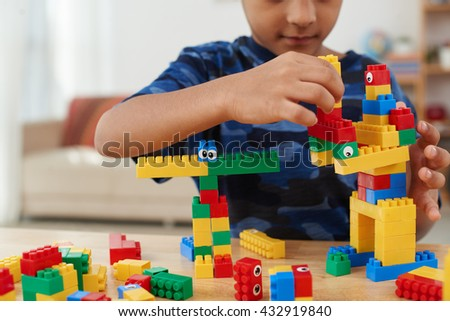 Cropped image of child making creatures out of plastic bricks