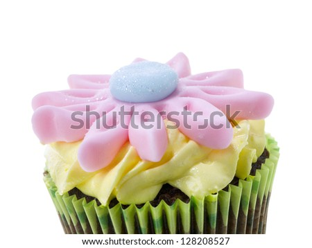 Cropped image of chocolate flavor cupcake with creamy icing and flower candy on top