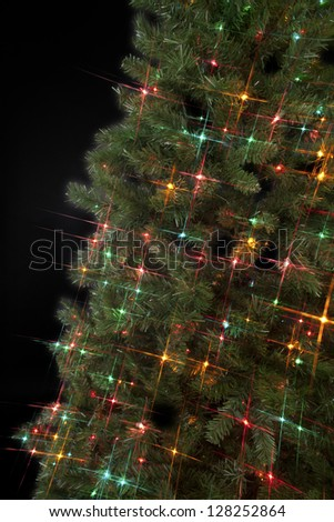 Cropped image of Christmas tree with decorative lights over dark background. - stock photo
