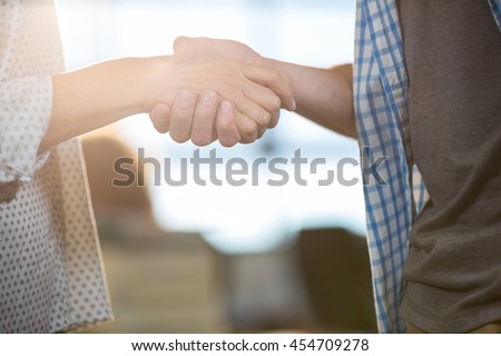 Cropped image of colleagues shaking hands in creative office