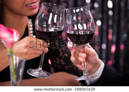Cropped image of couple toasting wineglasses in restaurant - stock photo
