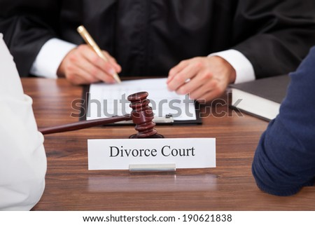 Cropped image of couple with judge writing at desk in court - stock photo