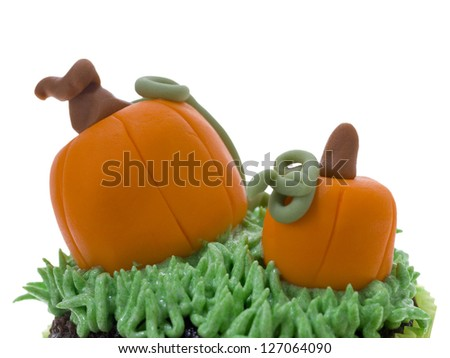 Cropped image of cupcake top with squash decoration on a white background - stock photo