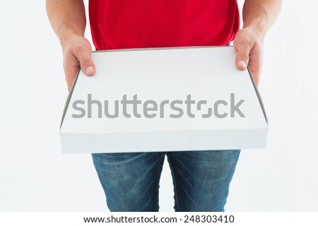 Cropped image of delivery man holding pizza box on white background - stock photo