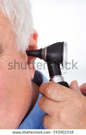 Cropped image of doctor examining senior man's ear with otoscope against white background - stock photo