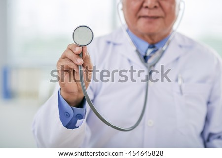Cropped image of doctor holding stethoscope in front of him