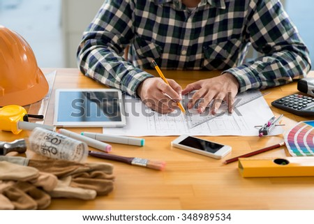 Cropped image of engineer working on plan of the building - stock photo