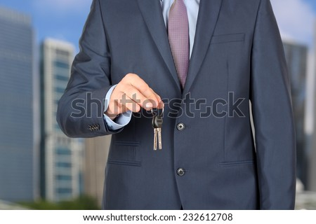 Cropped image of estate agent giving house keys outside  - stock photo