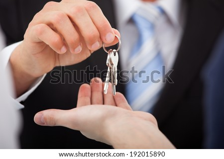 Cropped image of estate agent giving house keys to man in office - stock photo