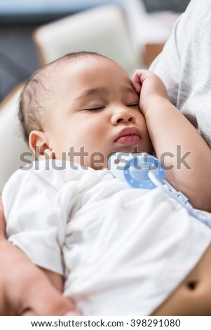 Cropped image of father carrying sleeping baby at home