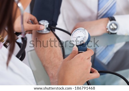 Cropped image of female doctor checking businessman's blood pressure in clinic