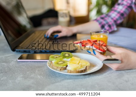 Cropped image of female hand holding healthy fruit sandwich while working on a computer on office table