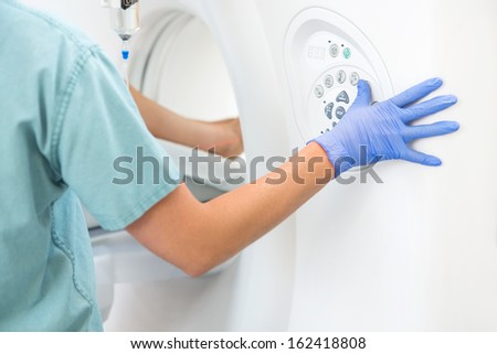 Cropped image of female nurse operating CT scan machine in examination room - stock photo