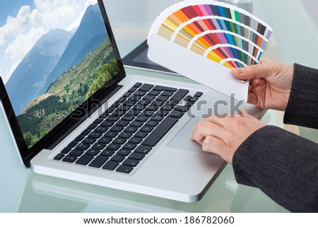 Cropped image of female photo editor holding color swatches while using laptop at desk