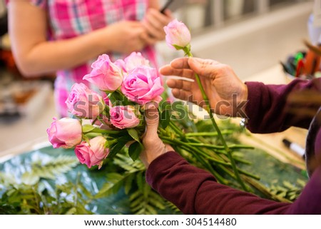 Cropped image of female worker making bouquet of roses for customer in flower shop - stock photo