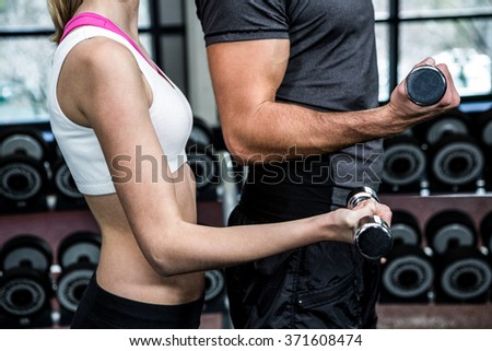 Cropped image of fit couple lifting dumbbells at gym - stock photo
