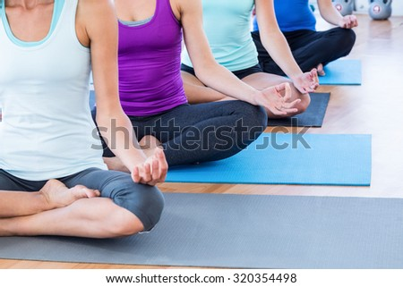 Cropped image of fit women doing easy pose in fitness studio - stock photo