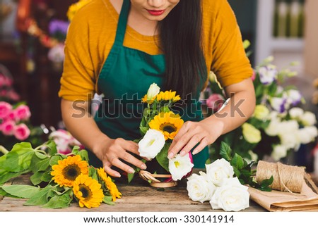 Cropped image of florist arranging flowers in the shop