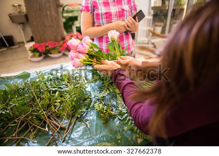 Cropped image of florist making bouquet of roses for female customer in flower shop - stock photo