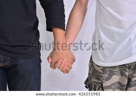 cropped image of gay couple holding hands on a white background.