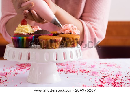 cropped image of girl decorating cupcakes