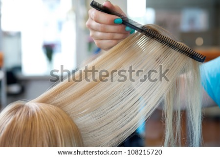 Cropped image of hairdresser's hand combing hair of female customer at salon