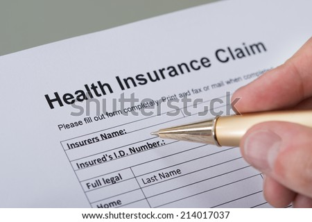 Cropped image of hand filling health insurance form on desk