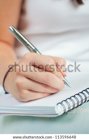 Cropped image of hand of young woman taking notes - stock photo