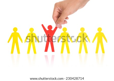 Cropped image of hand selecting red paperman representing recruitment against white background - stock photo