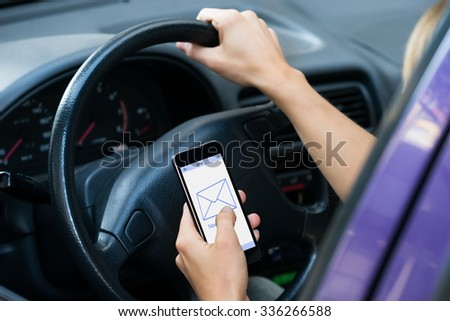 Cropped image of hands checking message while driving car - stock photo