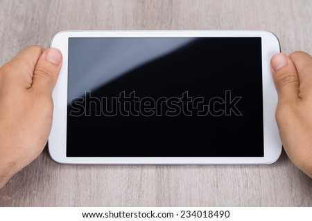 Cropped image of hands holding smartphone at wooden table - stock photo