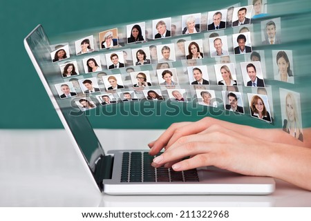 Cropped image of hands using laptop with businesspeople collage - stock photo
