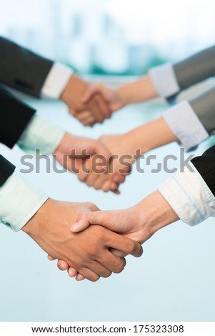 Cropped image of handshaking on the foreground  - stock photo