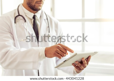 Cropped image of handsome Afro American doctor in white coat using a tablet, standing in office - stock photo