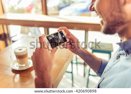 Cropped image of handsome young man making photo of his hot coffee drink using a smartphone and smiling while sitting in the cafe - stock photo