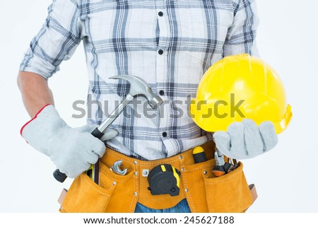 Cropped image of handyman holding hammer and hard hat over white background - stock photo