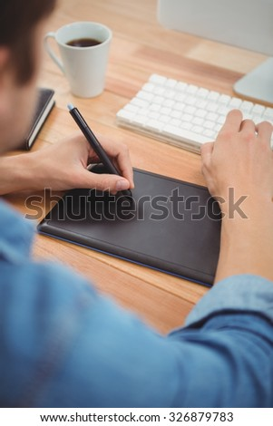 Cropped image of hipster using graphics tablet while typing on keyboard at table in office