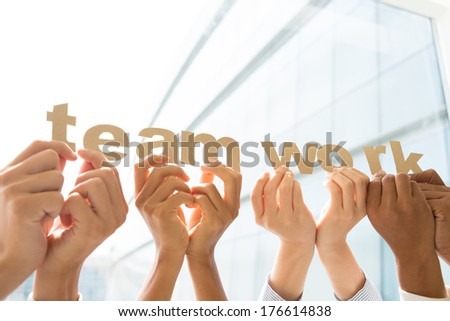 "Cropped image of human hands holding ""??teamwork""?� letters  - stock photo"