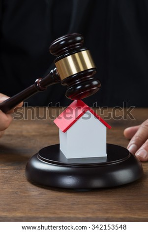 Cropped image of judge holding gavel on house model at desk - stock photo