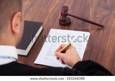 Cropped image of judge signing document in courtroom - stock photo