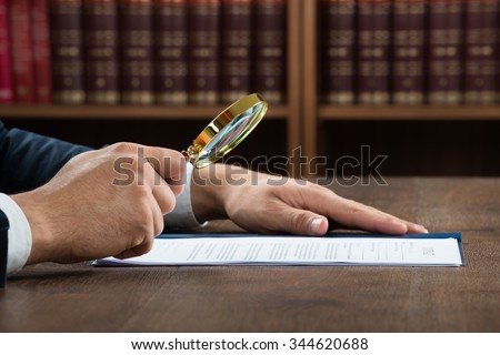 Cropped image of lawyer examining documents with magnifying glass in courtroom - stock photo