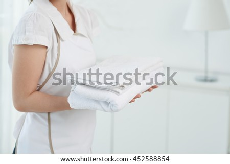 Cropped image of maid with fluffy white towels